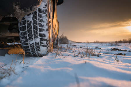 Car tires on winter road photo