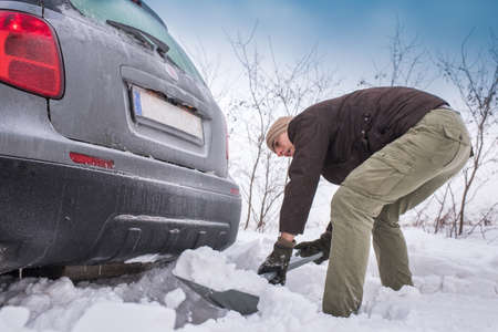 stuck: man digging up stuck in snow car Stock Photo