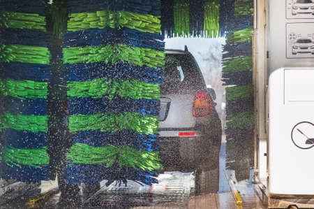 autolavaggio: Automobile grigia durante il processo di lavaggio