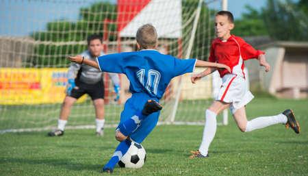 Muchachos patadas de fútbol en el campo de deportes