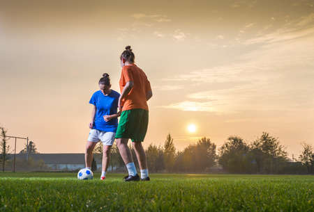 women playing soccer: Two female soccer players on the field