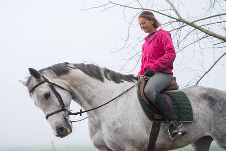 parapente: mujer joven a caballo en la niebla