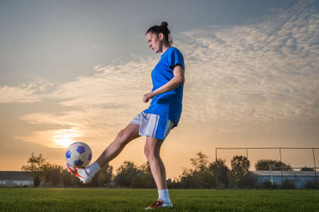 female kick: young woman kicking soccer ball