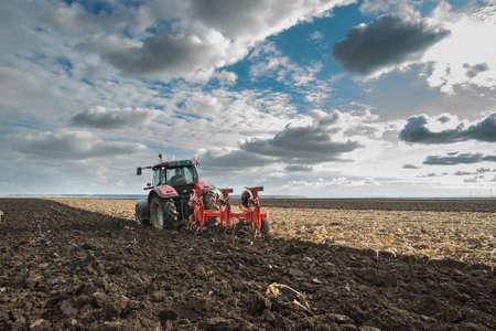 arando: Red Tractor Arando en el otoño