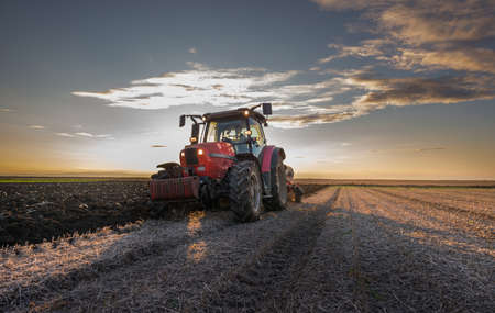 Tractor plowing at sunset