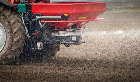 フィールドでトラクター、肥料スプレッダー 写真素材