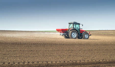 Tractor and fertilizer spreader in field photo