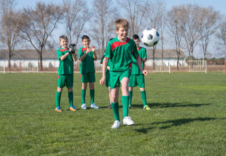 children only: Boys kicking football on the sports field Stock Photo