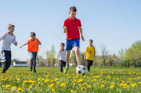 フィールドでサッカーを蹴る少年