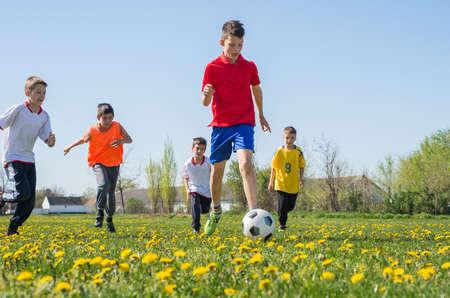 enfant qui joue: Gar�ons coups de pied football sur le terrain