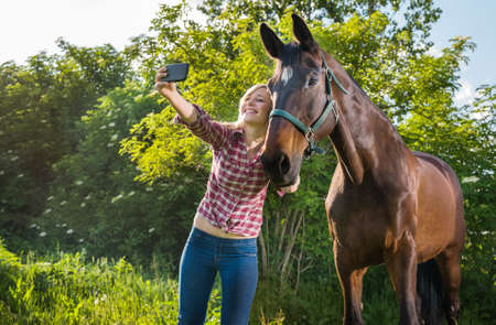 horse blonde: girl taking a selfie with his horse
