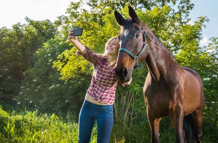 femme a cheval: jeune fille de prendre un selfie avec son cheval