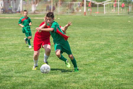 niños jugando: muchachos patadas de fútbol en el campo de deportes