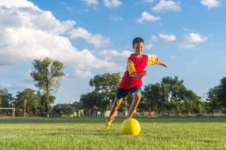 elementary age boys: Little Boy Kicking ball at Goal Stock Photo