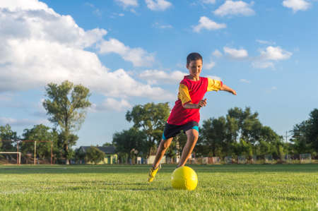 pelota de futbol: Little Boy Kicking pelota a portería Foto de archivo