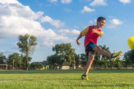 kicking ball: Little Boy Kicking ball at Goal Stock Photo