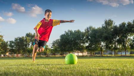 kicking: Little Boy Kicking ball at Goal Stock Photo