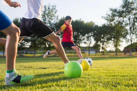 sports field: Boys kicking ball at goal