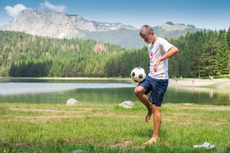 Soccer player juggles the ball in nature