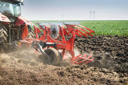 arando: Tractor arando el campo de rastrojo