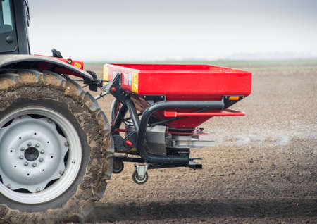 fertilizer: Tractor and fertilizer spreader in field