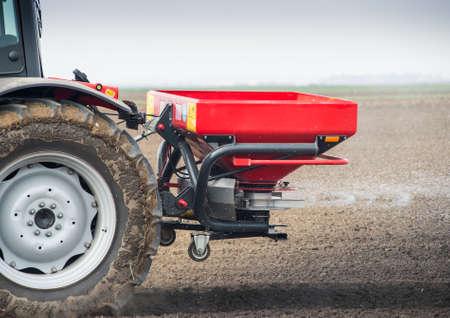 a crop: Tractor and fertilizer spreader in field