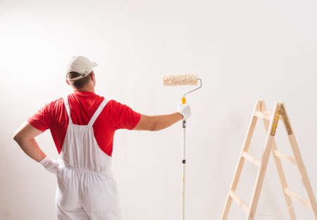 Young Man On Painting Wall With Roller Imagens