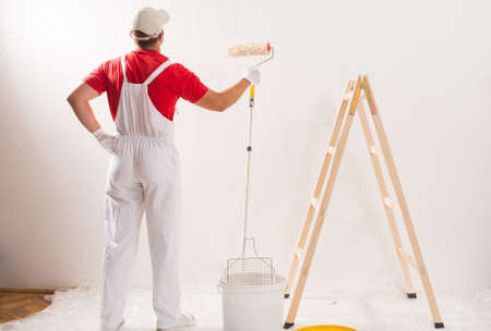 paint wall: Young Man On Painting Wall With Roller Stock Photo