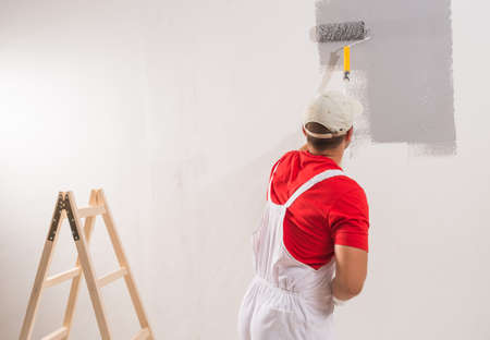 wall paintings: Young Man On Painting Wall With Roller Stock Photo