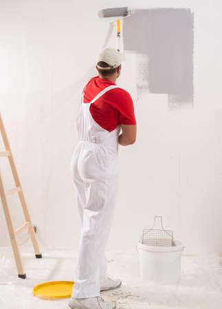 若い男がローラーで壁の塗装