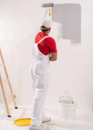 Young Man On Painting Wall With Roller Stock fotó
