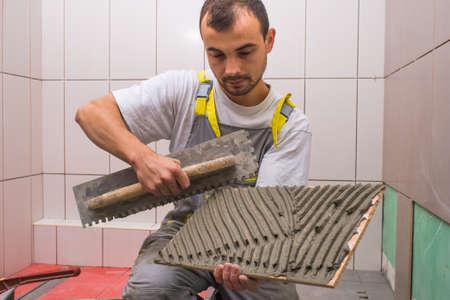 tile: Install ceramic tiles in bathroom Stock Photo