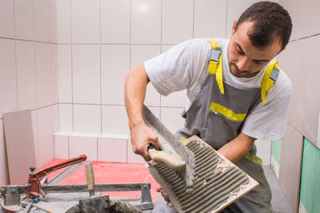 construction material: Install ceramic tiles in bathroom Stock Photo