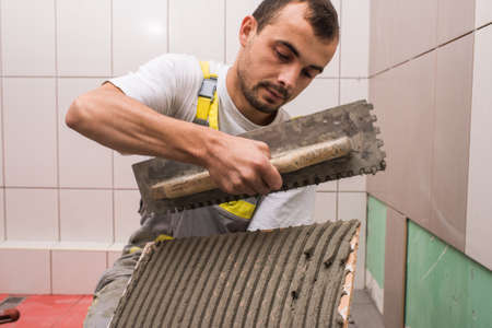 worker construction: Install ceramic tiles in bathroom Stock Photo