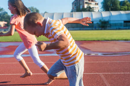 child couple: Happy girl and boy run on the track Stock Photo