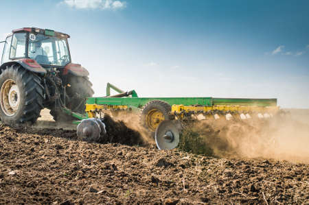 plough land: Tractor preparing land for sowing Stock Photo