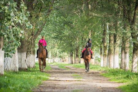 femme et cheval: Les filles sur une promenade à cheval.