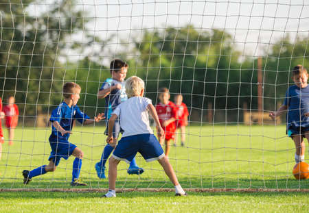 soccer pitch: Young boys play football match Stock Photo