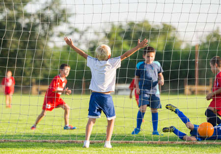 boys playing: Boy In Football Team Celebrating Stock Photo