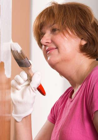 brush painting: Woman painting door with brush