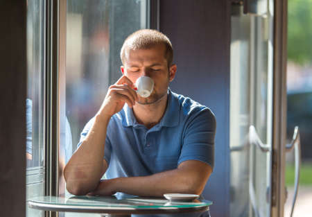 hombre tomando cafe: Young man drinking coffee in a cafe