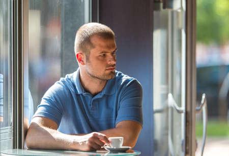 hombre tomando cafe: Hombre joven que bebe caf� en una cafeter�a