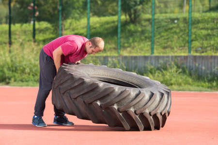 stamina: Young man does strongman exercise