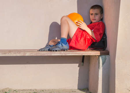child sport: portrait of a sad little boy in red soccer jersey seated on a bench and holding a ball