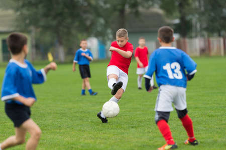 kids playing: boy kicking football on the sports field Stock Photo