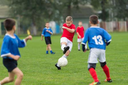jongen schoppen voetbal op het sportveld Stockfoto