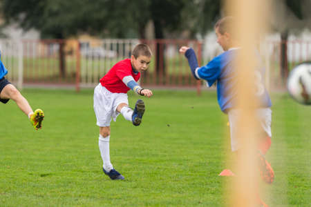 sports field: boy kicking football on the sports field Stock Photo