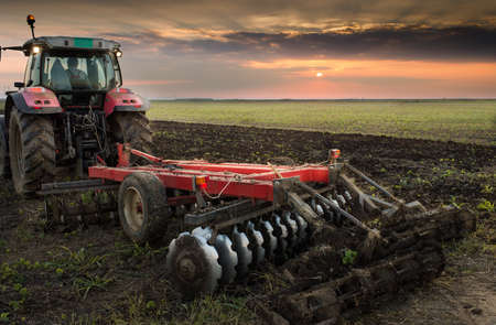 Tractor plowing a field at dusk Stock Photo - 47507045