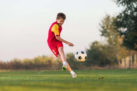 jugando: chico patear un balón de fútbol en el campo
