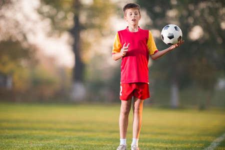 jugando futbol: Chico joven con balón de fútbol posando para la foto Foto de archivo